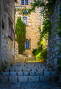"Street in Saint Paul de Vence in southern France.<br /> -----<br /> Saint-Paul or Saint-Paul-de-Vence is a commune in the Alpes-Maritimes department in southeastern France. One of the oldest medieval towns on the French Riviera, it is well known for its modern and contemporary art museums and galleries such as Fondation Maeght which is located nearby. It was probably between the 10th and 12th century that a settlement formed around the ancient church of Saint Michel du Puy to the south, and near the castle on the highest part of the hill. In the Middle Ages, the region was administered by the Counts of Provence. In the 13th century, Count Charles II granted more privileges to St. Paul, including the right to hold a weekly market. At the beginning of 14th century, St. Paul acquired more autonomy and became a prosperous city of merchants and nobility. In 1388, the County of Nice broke off from Provence to reattach itself with the states belonging to the Count of Savoy. These new circumstances gave St. Paul a strategic position: the city becomes a border stronghold for five centuries. St. Paul went through its first fortification campaign in the second half of 14th century: the north gate of the city, called ""Porte de Vence,"" dates back to the medieval wall. At the time of the wars of Italy, Provence was invaded twice by the troops of Charles V. Considering the low side of the border of Provence and the obsolescence of the medieval fortifications in Saint-Paul, Fran�ois 1st decided in 1538 to build the new city walls, able to withstand the power of the artillery. This fortified wall, built between 1543 and 1547, is preserved in its entirety. On its northern and southern fronts four solid bastions protect both the city gates. In the 17th century, Saint-Paul experienced a religious period through the influence of Antoine Godeau, Bishop of Vence. The church was elevated to college, and was expanded and embellished. St. Paul also saw an urban revival thanks to the families of nobili"