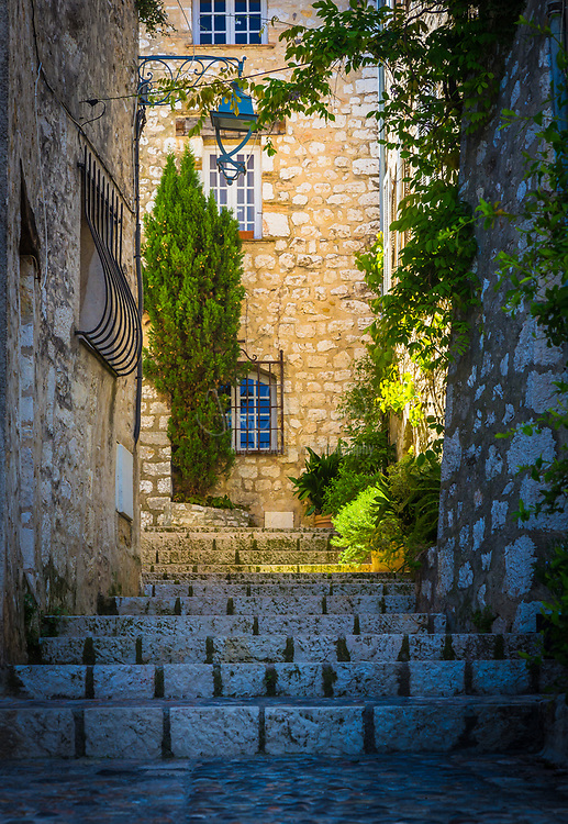"""Street in Saint Paul de Vence in southern France.<br /> -----<br /> Saint-Paul or Saint-Paul-de-Vence is a commune in the Alpes-Maritimes department in southeastern France. One of the oldest medieval towns on the French Riviera, it is well known for its modern and contemporary art museums and galleries such as Fondation Maeght which is located nearby. It was probably between the 10th and 12th century that a settlement formed around the ancient church of Saint Michel du Puy to the south, and near the castle on the highest part of the hill. In the Middle Ages, the region was administered by the Counts of Provence. In the 13th century, Count Charles II granted more privileges to St. Paul, including the right to hold a weekly market. At the beginning of 14th century, St. Paul acquired more autonomy and became a prosperous city of merchants and nobility. In 1388, the County of Nice broke off from Provence to reattach itself with the states belonging to the Count of Savoy. These new circumstances gave St. Paul a strategic position: the city becomes a border stronghold for five centuries. St. Paul went through its first fortification campaign in the second half of 14th century: the north gate of the city, called """"Porte de Vence,"""" dates back to the medieval wall. At the time of the wars of Italy, Provence was invaded twice by the troops of Charles V. Considering the low side of the border of Provence and the obsolescence of the medieval fortifications in Saint-Paul, Fran�ois 1st decided in 1538 to build the new city walls, able to withstand the power of the artillery. This fortified wall, built between 1543 and 1547, is preserved in its entirety. On its northern and southern fronts four solid bastions protect both the city gates. In the 17th century, Saint-Paul experienced a religious period through the influence of Antoine Godeau, Bishop of Vence. The church was elevated to college, and was expanded and embellished. St. Paul also saw an urban revival thanks to the families"""