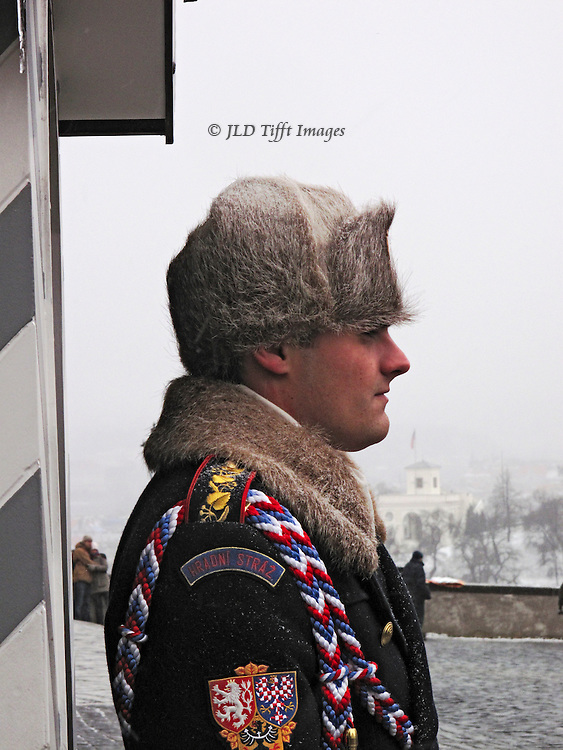 Bust in profile of a young man guarding an entrance to Hradcany Castle, Prague.  It is winter; his cheeks are rosy with cold and he wears a fur hat and the uniform has a fur collar.  Colorful insignia on the sleeve.