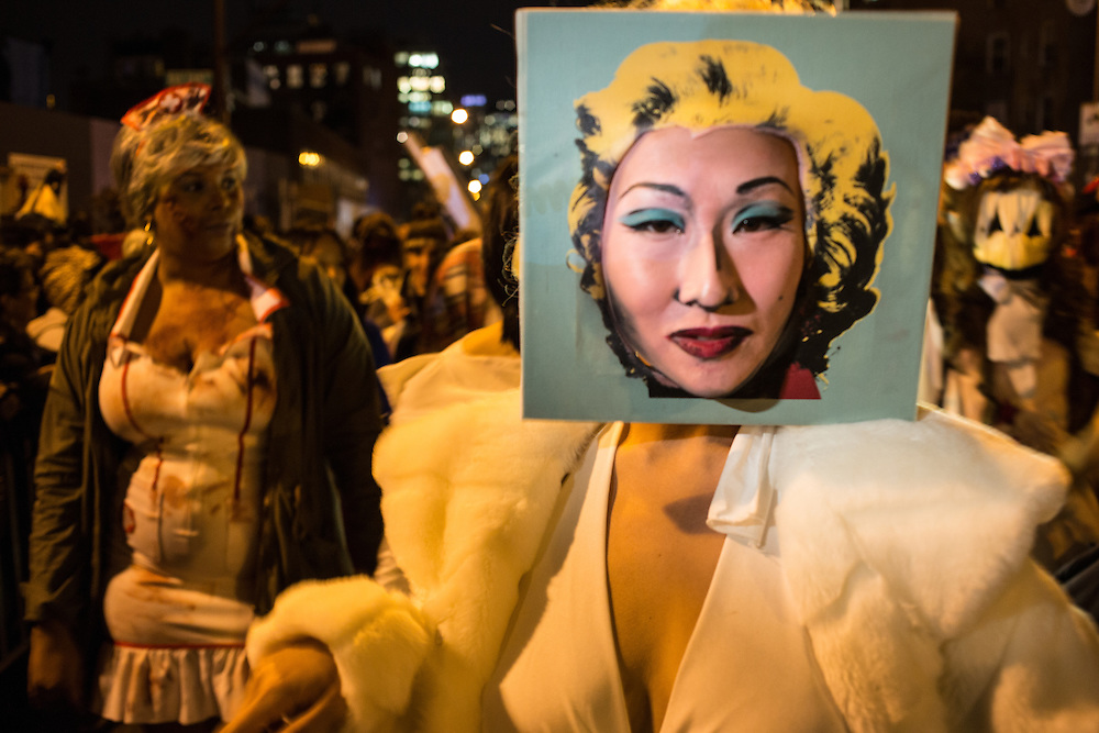 New York, NY, October 31, 2013. A woman wearing a relica of an Andy Warhol portrait of Marilyn Monroe with her actual face replacing Monroe's face in the Greenwich Village Halloween Parade.