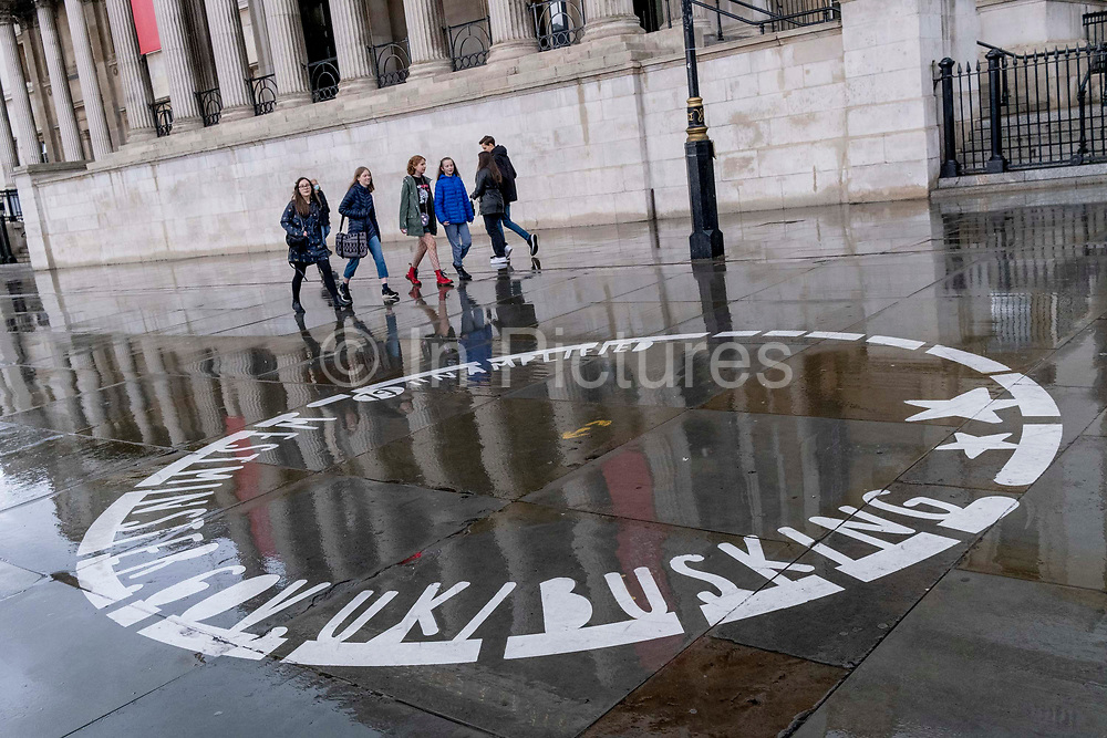 After seasonal Spring rainfall, Londoners walk past an empty buskers circle, on the paved area in front of the National Gallery in Trafalgar Square on 24th May 2021, in London, England.