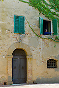 Woman opens window shutters of house covered in Virginia Creeper, in hill town of Monticcheillo, Val D'Orcia area of Tuscany, Italy