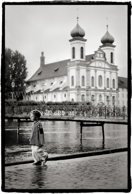 Black and White image of a boy outside of the Jesuitenkirche in Lucerne, Switzerland