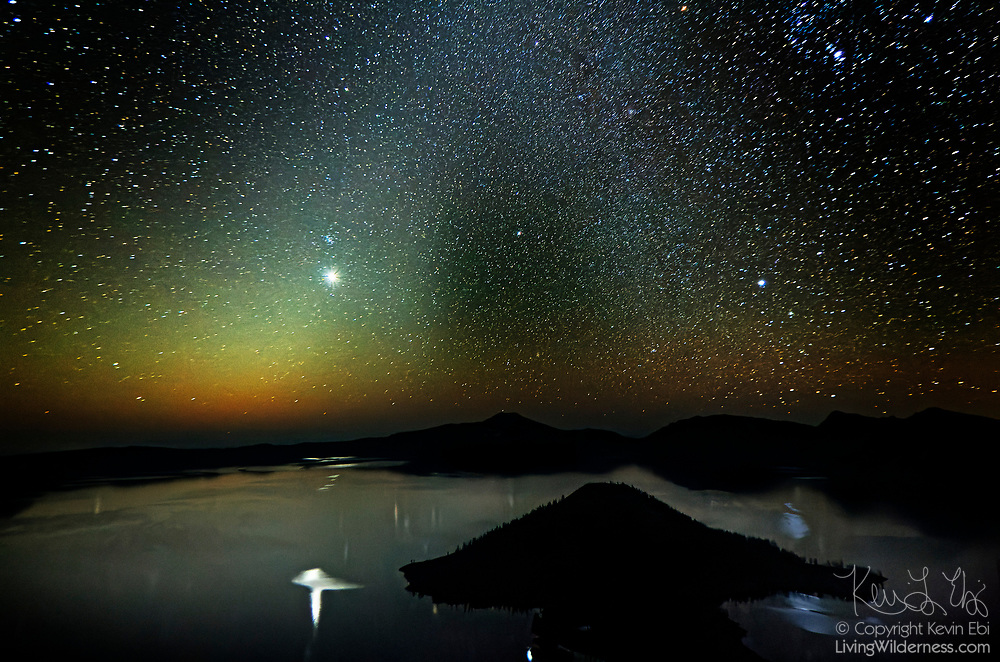 A natural nighttime pillar of light known as the Zodiacal Light shines above and is reflected in Crater Lake, Oregon. The Zodiacal Light results from the sun shining on dust particles left behind by comets. The dust particles - the largest of which are believed to be just 0.3 mm and miles from its nearest neighboring particle - orbit the sun in a range from Mars to beyond Jupiter. Visible year-round in the tropics, the Zodiacal Light is best viewed immediately around the spring and fall solstice farther from the equator. The planet Venus, the brightest object in the sky, is visible near the peak of the Zodiacal Light and is also reflected in Crater Lake. The Milky Way, visible on the right, intersects with the Zodiacal Light at the top-center of the image. Crater Lake, which is actually a caldera, formed when Mount Mazama erupted violently about 7,700 years ago, causing its summit to collapse. Subsequent eruptions sealed the caldera, trapping rain water and snowmelt, forming the lake, which has a maximum depth of 1,949 feet (594 meters). Wizard Island, a volcanic cinder code, is visible in the foreground.