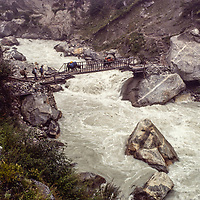 Sherpa guides herd a train of yaks across Nepal's Dudh Kosi River on a precarious cantilevered bridge.  This entire scene was wiped out a few years later by a massive outburst flood from a glacial lake near the base of Mount Everest.  (photo taken in 1980)