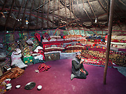 The interior of a yurt with a man drinking tea.<br /> Blankets filled with yak and sheep wool pile up against the inside wall of the yurt to insulate it from the constant winds. The floor carpet - bartered against 2 sheep - was acquired by Toorsoon in the lower valleys of Pakistan, a 10 days round trip leading over a 5000m pass. The wooden poles – over hundred years old - are handed over, generation after generation.<br /> <br /> At the Kyrgyz settlement of Bozoi Gumbaz, before Chaqmaqtin lake, Amon Boi's camp.<br /> <br /> Trekking through the high altitude plateau of the Little Pamir mountains (average 4200 meters) , where the Afghan Kyrgyz community live all year, on the borders of China, Tajikistan and Pakistan.