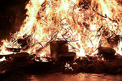 © Licensed to London News Pictures. 31/12/2016. Allendale, UK.  Empty barely lay in the bonfire following the procession of guisers in costume which paraded through the town of Allendale in Northumberland bearing aloft half-barrels filled with tar and flames. The annual Allendale Tar Barrel, or Tar Barl, event is a traditional custom which takes place on the eve of December 31st and welcomes in the new year. Photo credit : Ian Hinchliffe/LNP
