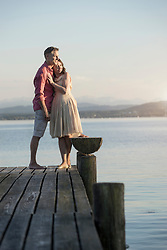 Mature couple standing on pier and looking over lake, Bavaria, Germany