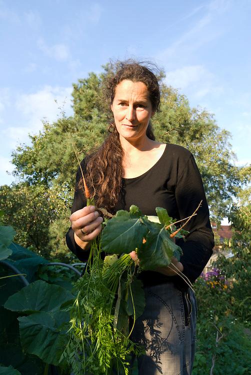 Eine Frau im Alter von Mitte vierzig Jahren steht in einem privaten Garten und zeigt mit  Bedauern eine winzige Möhre|  A woman at the age of 45 stands in her garden with some fresh harvested vegetable and is showing a very thin carrot