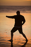 One mid adult man practices Taekwondo on the beach at sunset in Morro Bay, California.