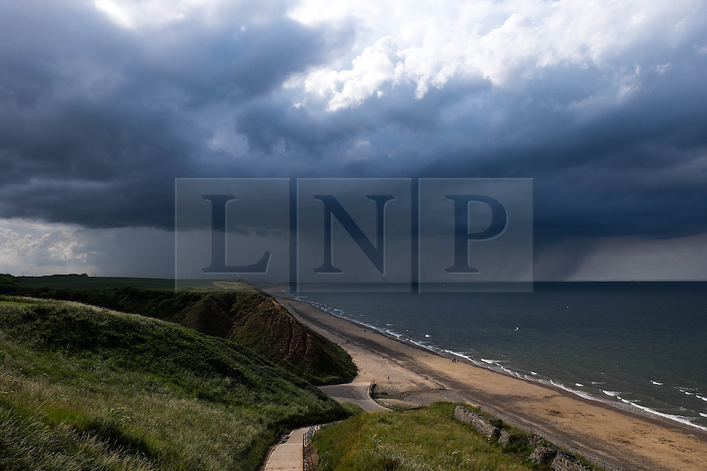 © Licensed to London News Pictures.05/07/15<br /> Saltburn by the Sea, UK. <br /> <br /> Sun light shines down on the beach as storm clouds pass over the north sea off the coastline at Saltburn by the Sea. <br /> <br /> Photo credit : Ian Forsyth/LNP