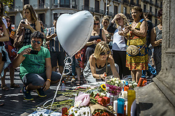 August 18, 2017 - Barcelona, Catalonia, Spain - A mourner places a candle at a makeshift memorial at the beginning of Las Ramblas where a van started a 550 meter long jihadist terror trip. Thirteen people were killed and almost 80 wounded, 15 seriously, when the van tore through the crowd (Credit Image: © Matthias Oesterle via ZUMA Wire)