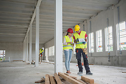 Construction workers with digital tablet and document at building site, Munich, Bavaria, Germany