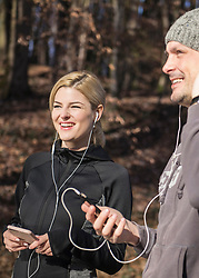 Man and woman in sportswear listening music on smart phone in forest
