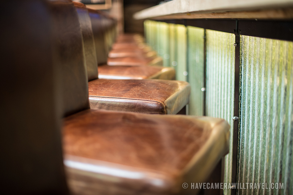 A row of brown leather bar stool chairs lined up next to a bar at a tavern.