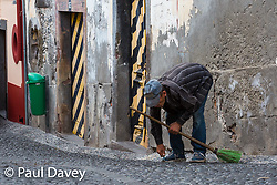 A street cleaner uses a blade to clean between cobble in a street in the old Town of Funcahal, Madeira. MADEIRA, September 25 2018. © Paul Davey