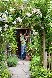 Putting up a hanging basket of begonias by a front door
