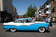 Blue and white vintage American car passes Portobello Road Market in Notting Hill, West London, England, United Kingdom. People enjoying a sunny day out hanging out at the famous Sunday market, when the antique stalls line the street.  Portobello Market is the worlds largest antiques market with over 1,000 dealers selling every kind of antique and collectible. Visitors flock from all over the world to walk along one of Londons best loved streets.