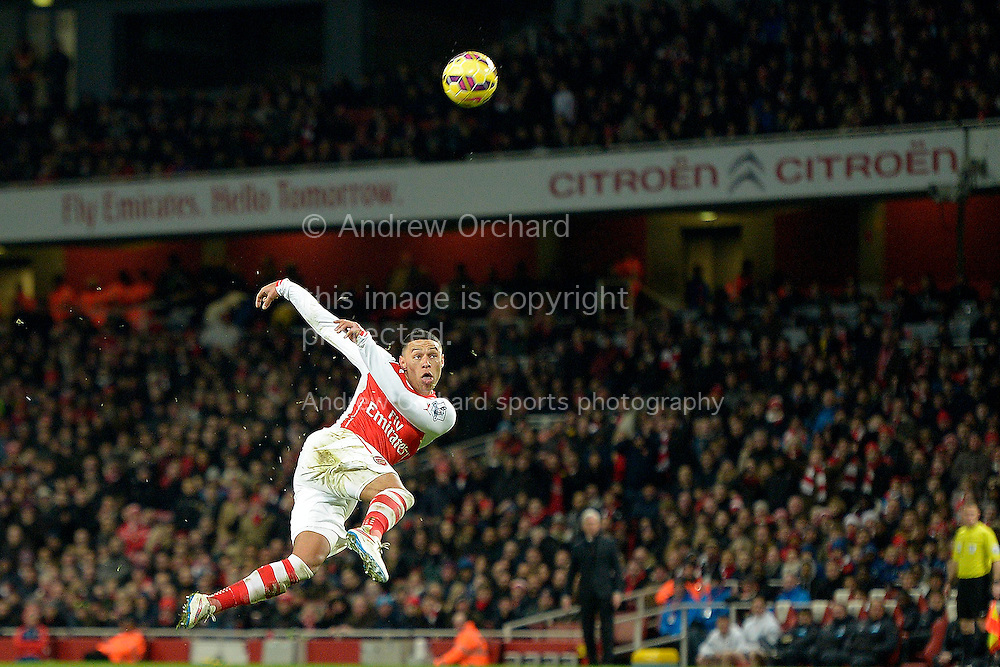 Alex Oxlade-Chamberlain of Arsenal shoots with a volley from outside the box. Barclays Premier league match, Arsenal v Newcastle Utd at the Emirates Stadium in London on Saturday 13th December 2014.<br /> pic by John Patrick Fletcher, Andrew Orchard sports photography.