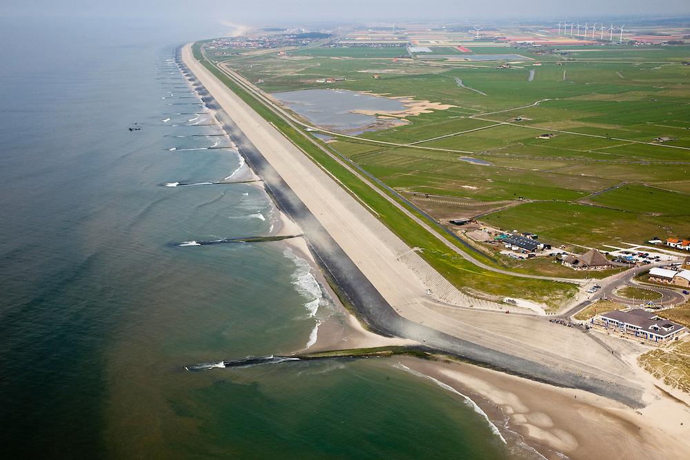 Nederland, Noord-Holland, Gemeente Schoorl, 28-04-2010; Hondsbossche zeewering gezien naar het noorden, Petten en de duinen aan de horizon. Rechts van de zeedijk de Vereenigde Harger- en Pettemerpolder met 'De Putten' (ontstaan in het verleden door het uitgegraven grond om de  zeewering te verstevigen). De dijk is aangelegd als zeewering nadat de oorsrponkelijke duinen weggeslagen waren. Door erosie kalven de duinen langs de kust steeds verder af, de dijk steekt daardoor steeds meer uit in zee..Hondsbossche seawall seen to the north, Petten and the dunes on the horizon. Right side of the seawall and the United Harger Pettemer Polder with 'The Wells' (created in the past by using soil for strengthening the seawall). The dike was built as a seawall after the primal dunes were washed away. Because of erosion the dunes decrease in size, therefore the sewall sticks more and more out into the sea..luchtfoto (toeslag), aerial photo (additional fee required).foto/photo Siebe Swart