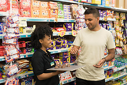 EMBARGOED TO 0001 MONDAY JUNE 26<br /> EDITORIAL USE ONLY<br /> Shopper Ajay Sharma tries a chocolate bar named 'Twin Peaks', as it launches at Poundland in Camden, London.