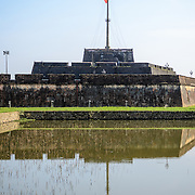 The large Vietnamese flag at the citadel is reflected on the defensive moat at the Imperial City in Hue, Vietnam. A self-enclosed and fortified palace, the complex includes the Purple Forbidden City, which was the inner sanctum of the imperial household, as well as temples, courtyards, gardens, and other buildings. Much of the Imperial City was damaged or destroyed during the Vietnam War. It is now designated as a UNESCO World Heritage site.