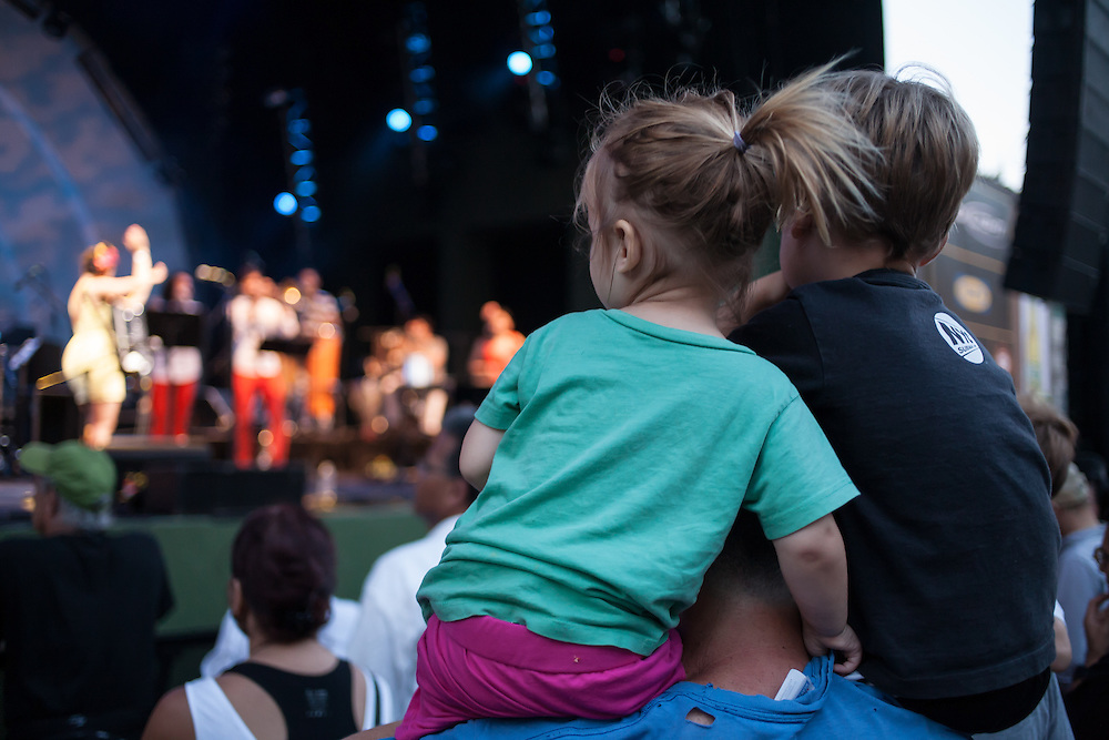 Two children sit on a man's shoulders to watch Banda Magda.