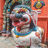 Ornate sculptures and paintings & a singh lion protect the main door to Hanuman Dhoka Palace in  the Durbar Square temple complex  in Kathmandu, Nepal.