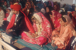 Bride and groom seated before their wedding ceremony in Patiala; Punjab; India,