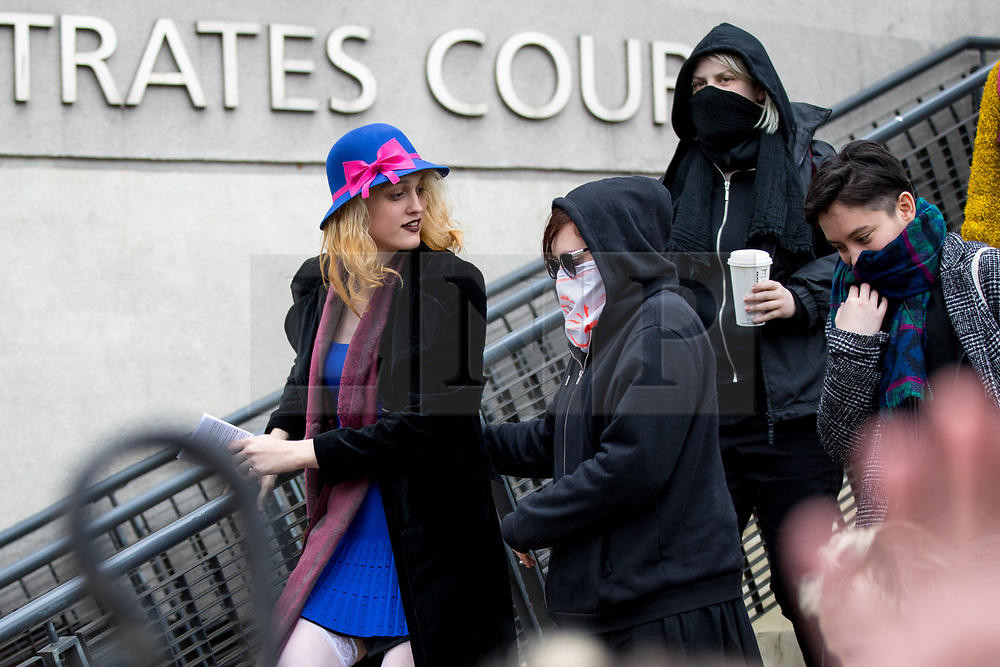 © Licensed to London News Pictures. 13/04/2018. London, UK. Transgender activist Tara Wolf (left) leaves Hendon Magistrates Court flanked by masked supporters, after being found guilty of assault by beating on the second day of her trial. The incident happened during a clash with Maria Maclachlan (not pictured) at Speakers' Corner, in Hyde Park last September. Wolf was given a £400 fine. Photo credit : Tom Nicholson/LNP