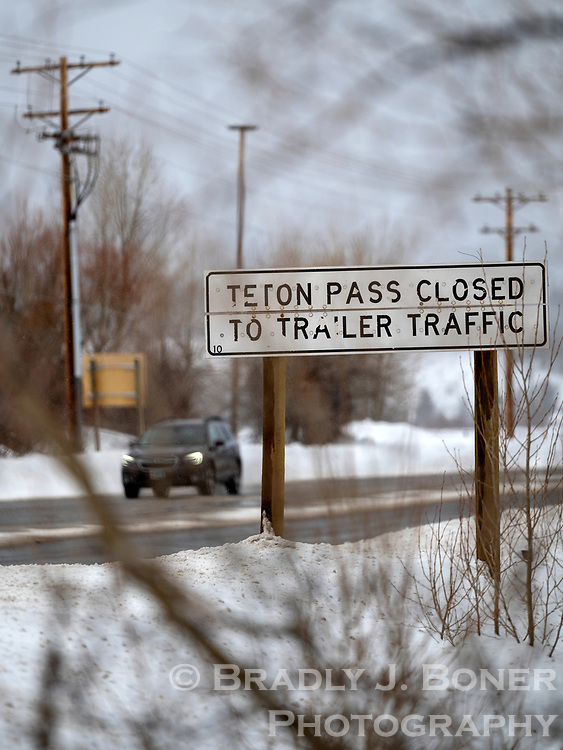 A sign along Highway 22 just west of the intersection with Highway 390 warns motorists that trailers are not allowed on Teton Pass in the winter. The sign folds horizonally and is closed when the trailer restriction is not in effect from April 1 to November 15.