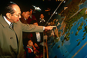 Families examine a map of the Hong Kong region, with outlying islands and mainland Chinese territories.