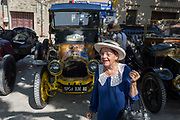 An elderly French lady and visiting vintage cars in a rural village, during a three-day rally journey through the Corbieres wine region, on 26th May, 2017, in Lagrasse, Languedoc-Rousillon, south of France. Lagrasse is listed as one of France's most beautiful villages and lies on the famous Route 20 wine route in the Basses-Corbieres region dating to the 13th century.