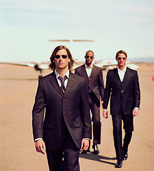 three men in suits and sunglasses walking at an airport in New Mexico
