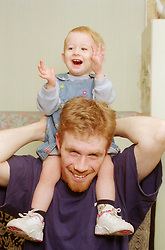Teenage father carrying young daughter on shoulders,