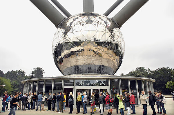 Belgie, Brussel, 28-7-2011Bezoekers staan in de rij voor het Atomium in Heyzel bij Brussel. Gebouwd voor de Wereldtentoonstelling van 1958. Het stelt een ijzerkristal voor. Het is het nationale symbool van Belgie geworden. The Atomium in Heysel in Brussels. The contribution of Belgium to the World Exhibition of 1958. It is an iron crystal. It is the national symbol of Belgium.