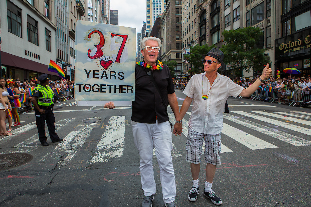 """A male couple walks down the parade route bearing a sign which reads """"37 years tgether."""""""