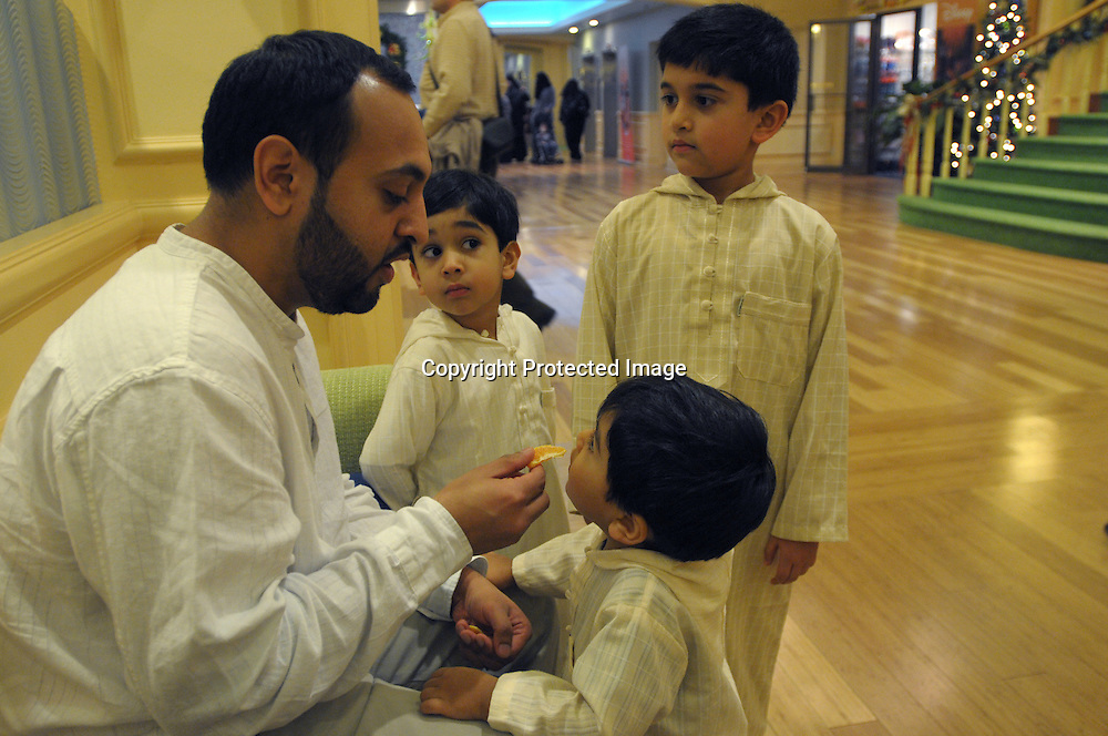 Kashif Irfan, left, feeds oranges to his sons Sinan, 2, Luqman, 4, and Murad, 7, inside the lobby of the Regal Sun Resort in Lake Buena Vista, Fla., Friday, Jan. 2, 2009.  The family were not allowed to board an AirTran flight from Washington, D.C. to Orlando after passengers mistook a conversation their group had about the safest place to sit aboard their plane. (Photo by Phelan M. Ebenhack)