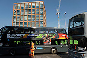 People, vehicles and buses passing the redeveloped area of Friargate and looking towards the building One Friargate in th UK City of Culture 2021 on 23rd June 2021 in Coventry, United Kingdom. This office space is home to Coventry City Council, which occupies the majority of floors, with the Financial Ombudsman Service occupying the remaining two. The UK City of Culture is a designation given to a city in the United Kingdom for a period of one year. The aim of the initiative, which is administered by the Department for Digital, Culture, Media and Sport. Coventry is a city which is under a large scale and current regeneration.