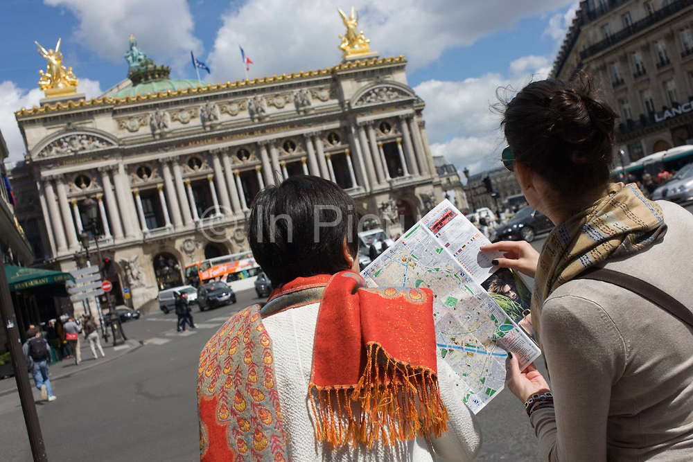 """Tourists consult a map opposite L'Opera - known as the Palais Garnier - in Paris, France. We look over the shoulders of the two tourists who are pointing and looking at the street plan of the French capital, on a summer's day. The Palais Garnier is a 1,979-seat opera house, which was built from 1861 to 1875 for the Paris Opera. It was originally called the Salle des Capucines because of its location on the Boulevard des Capucines in the 9th arrondissement of Paris. The Palais Garnier is """"probably the most famous opera house in the world, a symbol of Paris."""