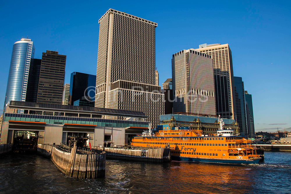 A famous orange Staten Island Ferry waits in the Whitehall Terminal in Lower Manhattan, New York City, New York, United States of America. The Staten Island Ferry is a passenger ferry service operated by the New York City Department of Transportation. It runs 5.2 miles 8.4 km in New York Harbor between the New York City boroughs of Manhattan and Staten Island. The ferry operates 24/7.
