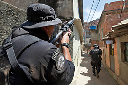 A Coordenação de Recursos Especiais da polícia (CORE), cobre os seus companheiros durante patrulha na favela Morro do Alemão em 29 de novembro de 2010 no Rio de Janeiro, Brasil. A polícia vasculhou os esgotos em favelas do Rio de Janeiro segunda-feira por centenas de traficantes de drogas que fugiu de um ataque militar sem precedentes sobre as favelas que rendeu 40 toneladas de entorpecentes, mas poucas prisões. A polícia vasculhou os esgotos em favelas do Rio de Janeiro segunda-feira por centenas de traficantes de drogas que fugiram de um ataque militar sem precedentes sobre as favelas cariocas que rendeu 40 toneladas de entorpecentes, mas poucas prisões. FOTO: Jefferson Bernardes/Preview.com