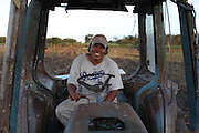 Renan Santos, 34, from Guinea Grass, drives a tractor that pulls a light harrow and fertilizer implement paid with Fairtrade premium funds that makes grooves and drops fertilizer pellets simultaneously on sugar cane fields. The grooves are made in order to dry up the nymphs of the Froghopper (Cercopoidea) through an environmental friendly manner without using pesticides. The Froghopper's nymph pierce sugar cane plants and suck sap, causing serious damage if uncontrolled. The increasing rains and unpredictable weather due to climate change are allowing the Froghopper's population to rise, posing serious danger to the BSCFA's producers. Belize Sugar Cane Farmers Association (BSCFA), Chen Pine Ridge, Orange Walk, Belize. January 21, 2013.