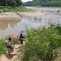 Women carrying heavy baskets in the heat of summer.
