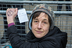 London, UK. 21st December, 2018. An environmental campaigner from Extinction Rebellion glued to railings outside Broadcasting House in protest against the lack of coverage by the BBC of the climate change crisis.
