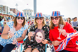 © Licensed to London News Pictures. 19/05/2018. Brighton, UK. (L to R) ANGELA PARKER, KIM CRONIN and MAUREEN WILCOCK from Brighton join hundreds of people on the beach in Brighton and Hove as they watch the wedding between HRH Prince Harry and Miss Rachel Meghan Markle live on a big screen on the beach in Brighton and Hove. Photo credit: Hugo Michiels/LNP