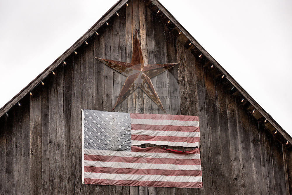 Old barn and American flag featuring the gallery of artist David Arms in Leipers Fork, Tennessee.