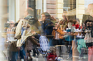 Numerous people, some in conversation, seen through a cafe window, as well as pedestrians on the sidewalk reflected in the window, in Sarajevo, Bosnia and Herzegovina