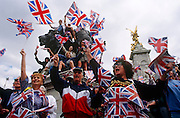 Crowds wave Union Jack flags below lion of Buckingham Palace's Victoria Memorial during VE Day anniversary celebrations.