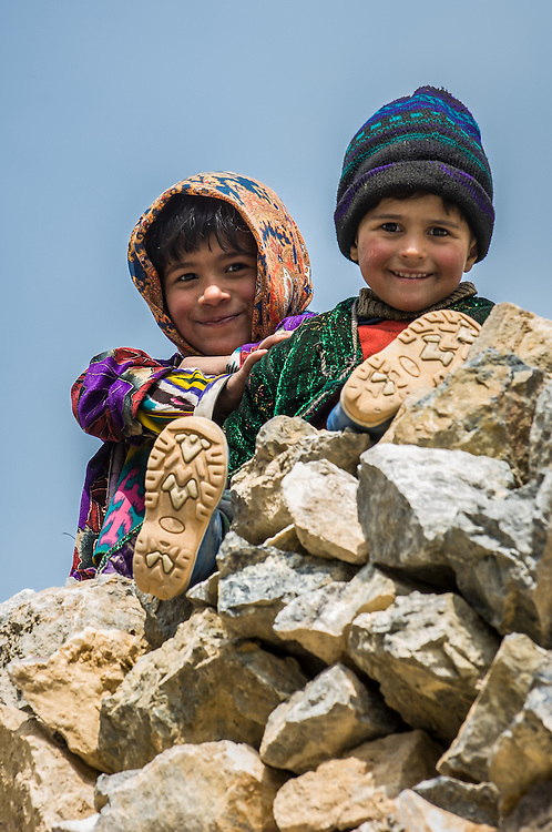 Portrait of young Tajik children peering curiously and cheerfully at the photographer from atop their home